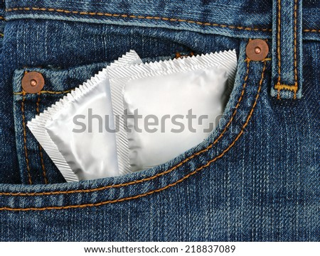 Condoms in the blue jeans pocket, macro - stock photo