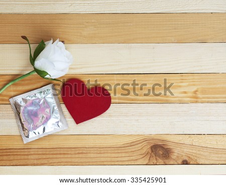 condoms, white rose and red heart on yellow background. dating concept image. light soft image - stock photo