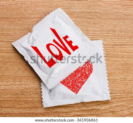 Condoms with text Love on wooden table - stock photo