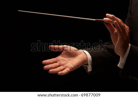 Conductor conducting an orchestra isolated on black background - stock photo