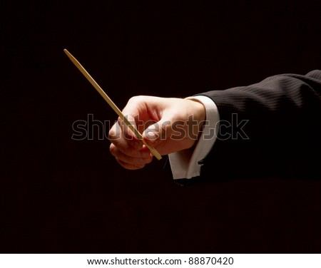 Conductor conducting orchestra isolated on black background - stock photo