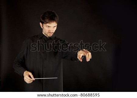 conductor on a black background with a big inspiration gets the job done - stock photo