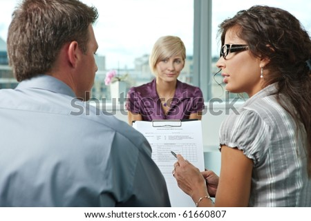 Conductors talking over the questionnaire form during the job interview. Over the shoulder view. Focus placed on the sheet in front. - stock photo