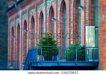 Cone-bearing evergreen tree with lights on forged iron balcony against brick wall building. Christmas bazaar in Bad Ems, germany.