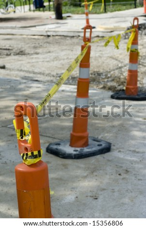 Cones and tape cordon off a bit of a street under construction.