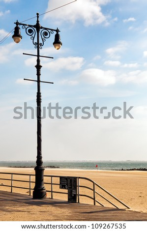 Coney Island vintage lamppost, boardwalk and beach.  Copy space - stock photo