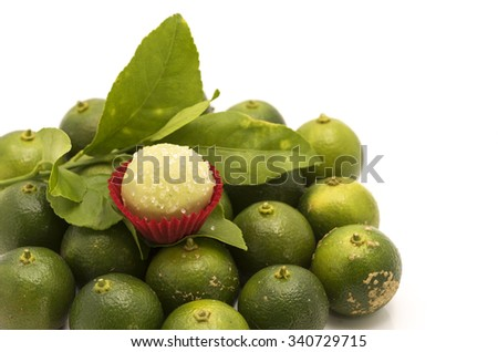 Confectionery of lime flavor. Focus on the candy ball covered with lime flavor chocolate and sugar in mini cake red paper cup.  Background is fresh limes and leaves on white. - stock photo