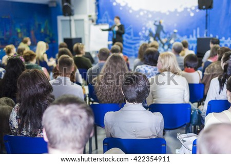 Conference Concept and Ideas. Female Lecturer Speaking In front of the Large Group of People. Horizontal Shot - stock photo