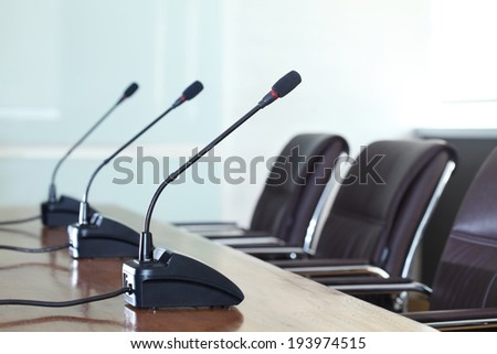 Conference microphones in a meeting room - stock photo