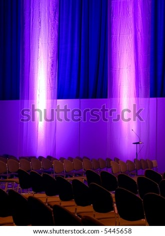 conference room with rows of chairs, blue curtains, purple drapes, microphones - stock photo