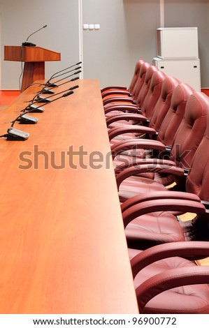 Conference table with microphones and leather armchairs - stock photo