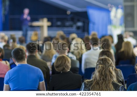 Conferences Concept and Ideas. Male Leader Lecturer Speaking In front of the Large Group of People. Horizontal Image Composition