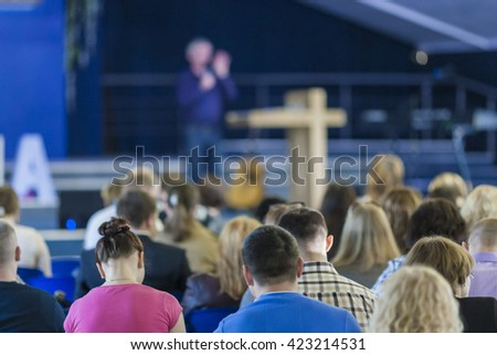 Conferences Concepts. Male Lecturer Speaking  On Stage In front of the Large Group of People. Horizontal Image Composition - stock photo