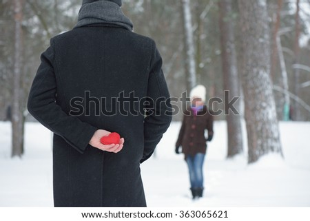 Confession of Love. Concept of Valentines Day. Surprise to woman. Man hiding behind a decorative heart - stock photo