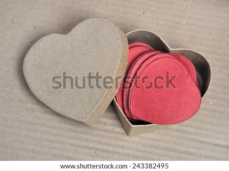 confetti in a recycled cardboard box heart shape on cardboard background - stock photo