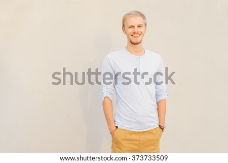 Confidence and charisma. Handsome young man holding hands in pockets and looking at camera while standing against grey background. - stock photo