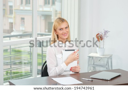 Confidence in business. Cheerful businesswoman working on the tablet. Charming blond girl sitting in the office looking into the camera. - stock photo
