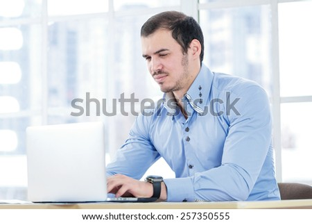 Confidence in business. Confident businessman working at a laptop and looking at the computer while pretty businesswoman sitting in office at the table in the formal wear.