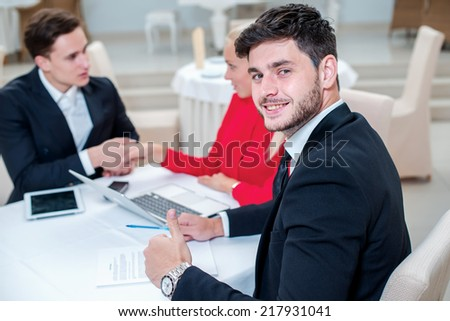 Confidence in the work. Successful and confident businessman discussing work at a laptop. Businesspeople in formal dress sitting in an office at a desk and smiling at the camera