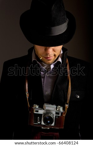 Confidence, young photographer with an old photocamera tape match in teeth in a hat - stock photo