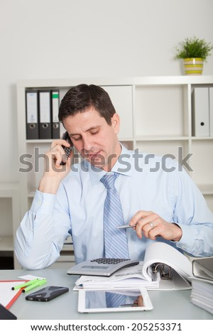 Confident accountant talking on mobile phone in order to communicate the results of his calculations, looking to an office calculator, placed on the desk next to folders, a smart phone and a tablet PC - stock photo