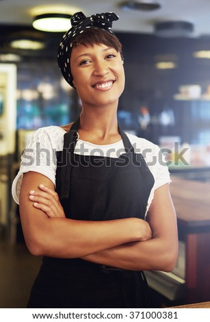 Confident African American female entrepreneur standing with folded arms in her shop looking at the camera with a lovely beaming friendly smile - stock photo