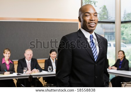 Confident African businessman standing in front of co-workers in conference room - stock photo