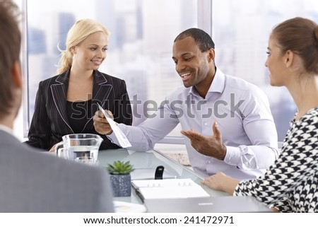 Confident afro businessman talking to partners at business meeting.