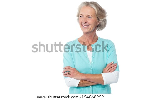 Confident aged woman in casuals, arms crossed.