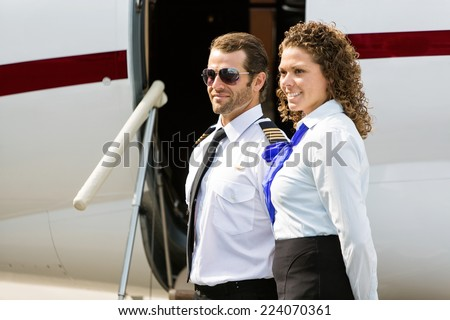 Confident airhostess and pilot looking away while standing against private jet - stock photo