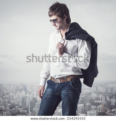 Confident, ambitious good looking man on the top of the city with a jacker on his shoulder - stock photo