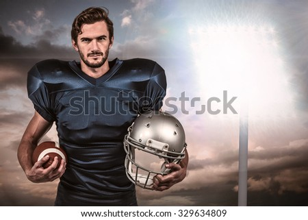 Confident american football player holding an helmet against spotlight in sky