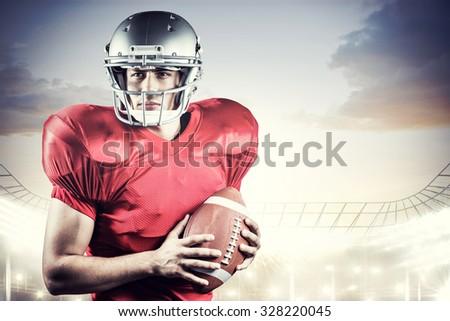 Confident American football player holding ball against rugby stadium