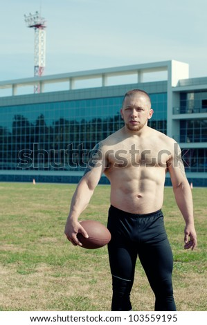 Confident american football player on the playfield - stock photo
