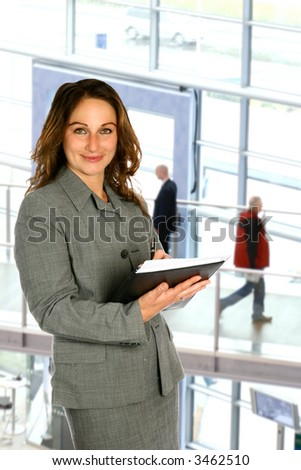 Confident and attractive sales representative holding notes and information, against modern corporate interior. - stock photo