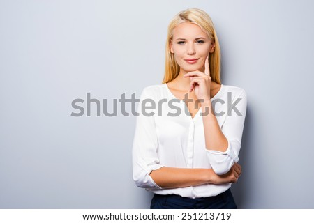 Confident and charming. Thoughtful young women holding hand on chin while standing against grey background - stock photo