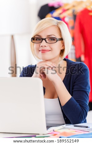 Confident and creative businesswoman. Beautiful young woman holding hands on chin and smiling while sitting at her working place - stock photo