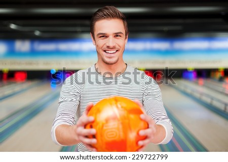 Confident and creative. Cheerful young man stretching out a bowling ball and smiling while standing against bowling alleys  - stock photo