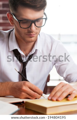 Confident and creative. Handsome young man in shirt and tie writing something in note pad while sitting at his working place - stock photo