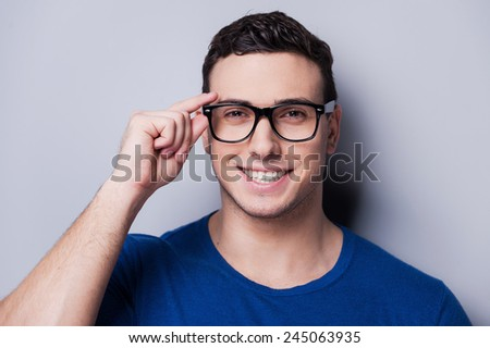 Confident and creative. Portrait of young man touching his grasses and looking at camera while standing against grey background.  - stock photo