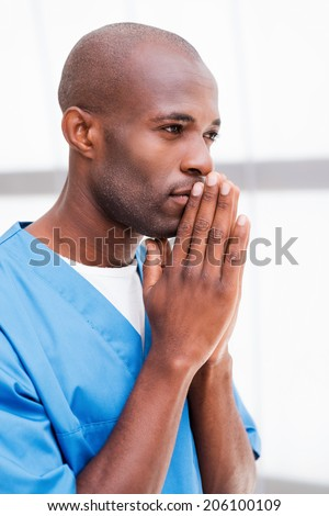 Confident and experienced surgeon. Side view of thoughtful young African doctor in blue uniform holding hands clasped near face and looking away and keeping arms crossed - stock photo