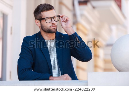 Confident and handsome. Handsome young man in smart casual wear adjusting his eyeglasses and looking away while standing outdoors - stock photo