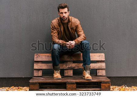 Confident and handsome. Handsome young man sitting on the wooden pallet and looking at camera with grey wall in the background and orange fallen leaves on the floor  - stock photo