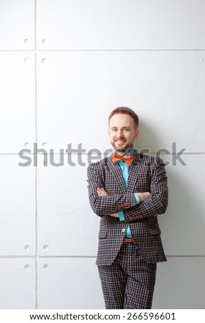 Confident and handsome. Portrait of  young bearded man in plaid suit and bowtie keeping arms crossed and looking at camera while standing against white wall. - stock photo