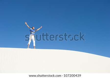 Confident and happy looking attractive mature woman jumping for joy on  desert sand dune lookout, isolated with blue sky as background and copy space. - stock photo