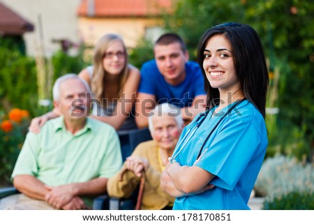 Confident and kind doctor welcoming the family members of the elderly patient. - stock photo