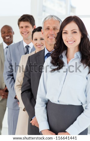 Confident and mature manager standing among his smiling employees - stock photo