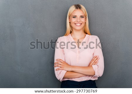 Confident and pure beauty. Beautiful young woman looking at camera and keeping arms crossed while standing against grey background - stock photo