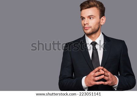 Confident and serious. Confident young man in formalwear holding hands clasped and looking away while standing against grey background - stock photo
