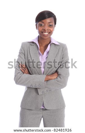 Confident and smiling in grey business suit, a portrait shot of beautiful young black business woman, standing with arms folded. - stock photo